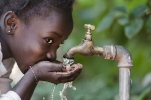 girl drinking clean water in Africa